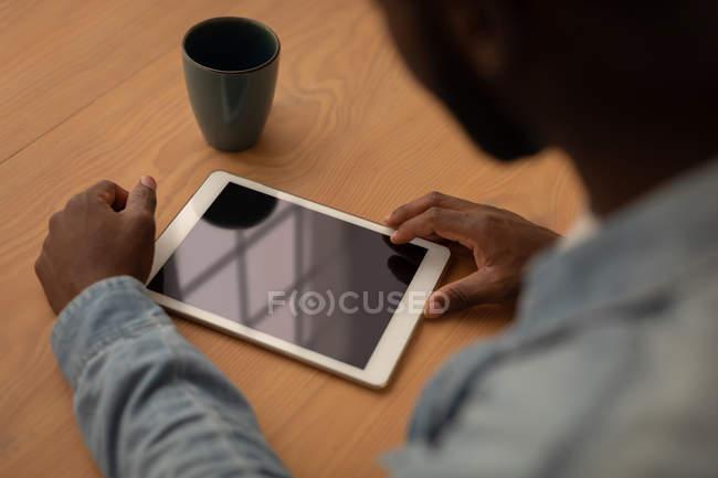 Высокий угол зрения афро-человека, с использованием цифрового планшета сидя на стуле в доме — стоковое фото