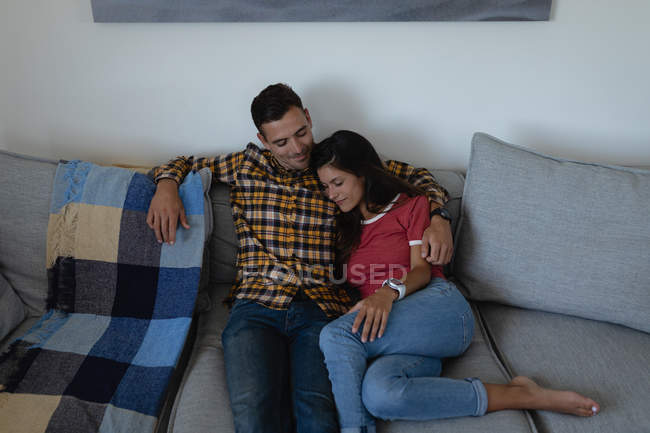 High angle view of young multi-ethnic couple relaxing and leaning on sofa at home — Stock Photo