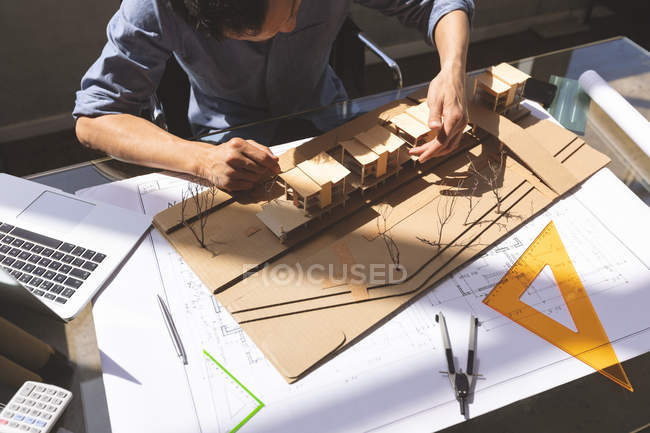 High angle view of Asian male architect working on architectural model at desk in a modern office — Stock Photo