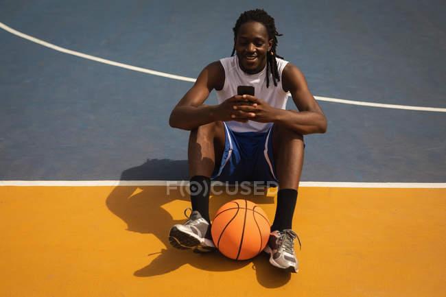 Высокий угол обзора улыбающегося афро-американского баскетболиста, сидящего на игровом полу с баскетбольным мячом между ног, пока он использует мобильный телефон на баскетбольной площадке — стоковое фото