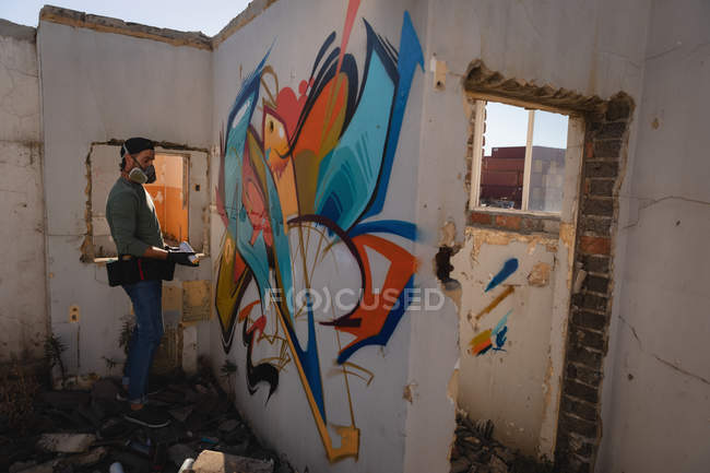 Side view of young Caucasian graffiti artist spray painting on weathered wall room at alley — Stock Photo