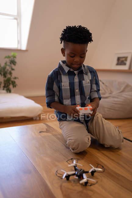 Vista frontal de lindo niño afroamericano jugando con abejón en la mesa en casa - foto de stock