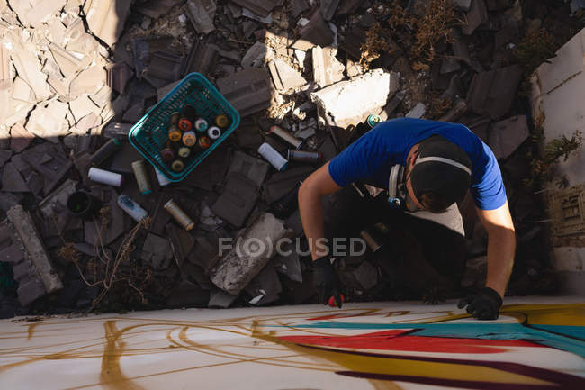 High angle view of young Caucasian graffiti artist spray painting weathered wall room — Stock Photo