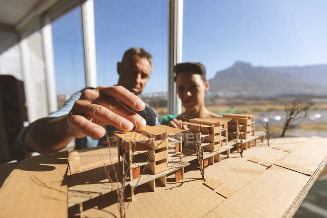 Front view of Caucasian architects discussing over architectural model while male architect touches the model against beautiful view — Stock Photo