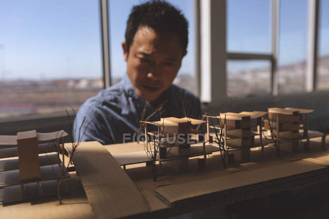 Front view of a male Asian architect looking at an architectural building model in a modern office — Stock Photo