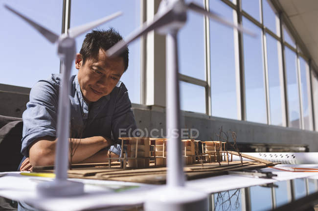 Front view of Asian male architect looking at architectural model on desk in a modern office — Stock Photo