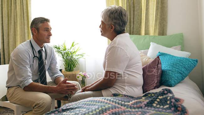Visão lateral do médico masculino caucasiano interagindo com a raça mista sênior paciente do sexo feminino em casa de repouso — Fotografia de Stock