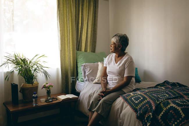 Вид сбоку старший печально смешанной расы женщина, сидя на кровати, в домах престарелых — стоковое фото