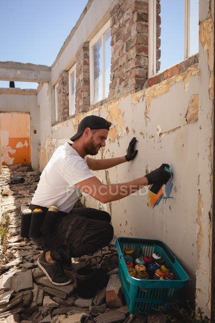 Side view of young Caucasian graffiti artist spray painting weathered wall at alley — Stock Photo