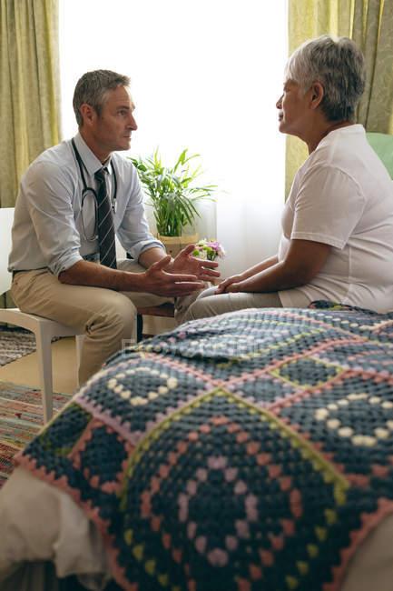 Vista laterale del medico maschio caucasico, interagendo con paziente femminile senior sangue misto presso Casa di riposo — Foto stock