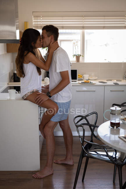 Side view of romantic multi-ethnic couple kissing each other in kitchen at home — Stock Photo
