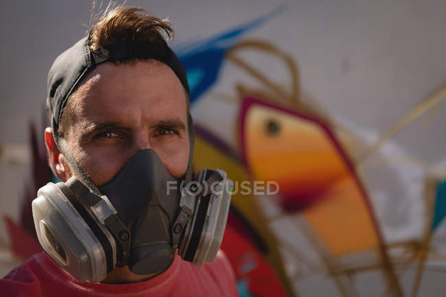 Portrait of young Caucasian graffiti artists standing with protective mask. He is smiling at camera — Stock Photo