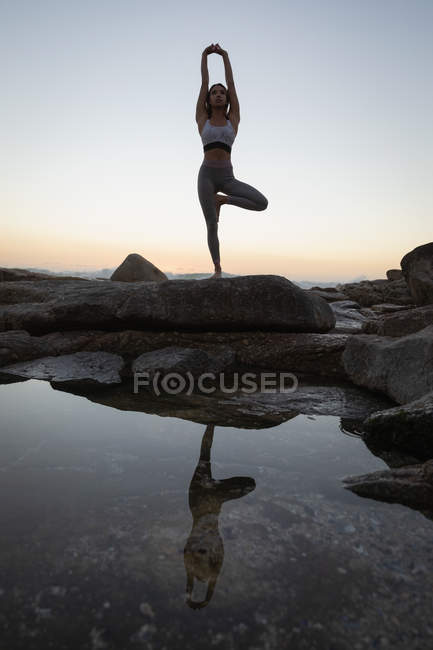 Low angle view of woman doing yoga on rock on the beach at sunset — Stock Photo
