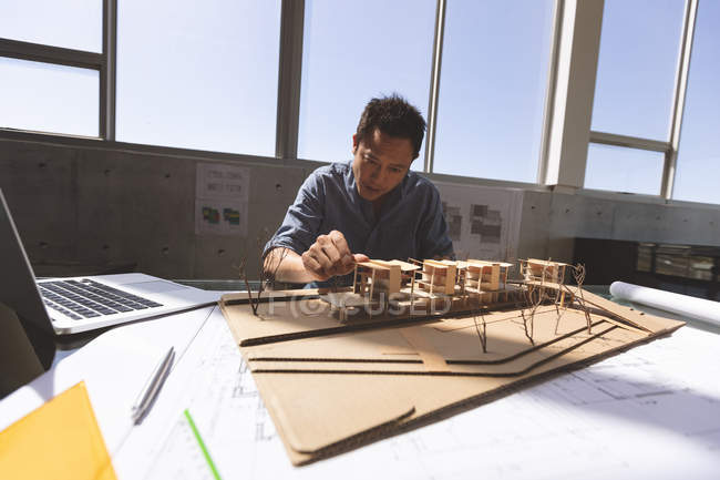 Front view of Asian male architect working on an architectural model at desk in a modern office — Stock Photo
