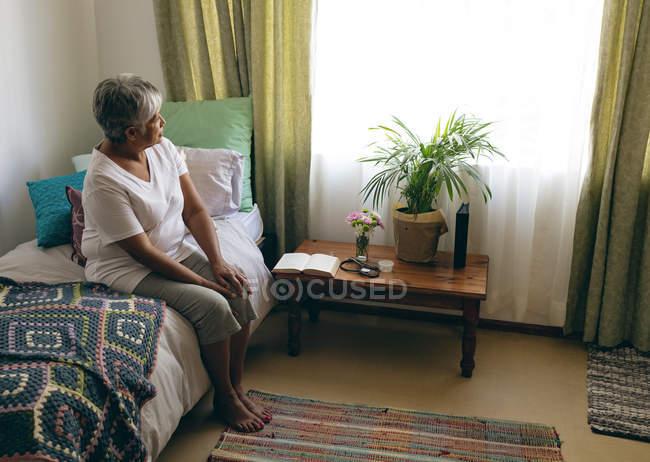 Вид сбоку вдумчивый старший смешанной расы женщина, сидя на кровати в спальне дома престарелых. Глядя в окно — стоковое фото