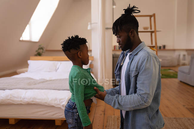 Вид сбоку на афроамериканского отца раздетого непослушного сына дома — стоковое фото