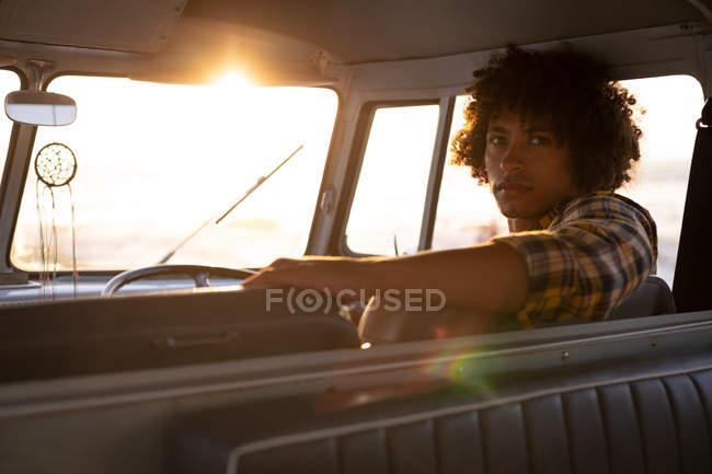 Задній вид змішана раса людини навернення до дивлячись камера в camper van проти sundown на пляжі — стокове фото