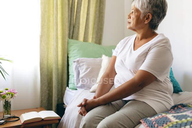 Вид сбоку вдумчивый старший смешанной расы женщина сидит на кровати и глядя в окно на доме престарелых — стоковое фото