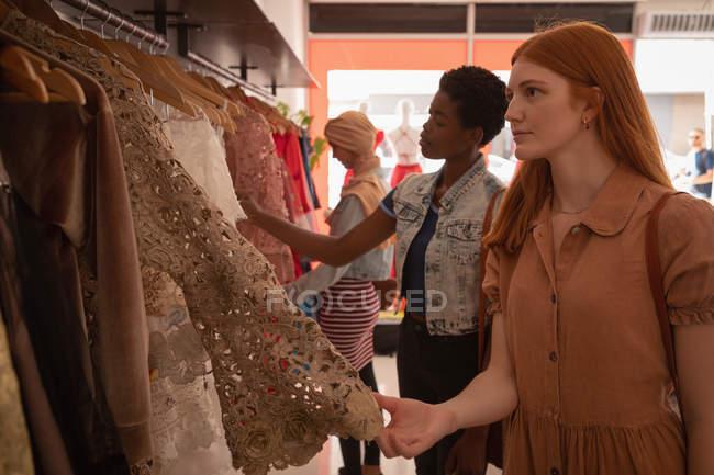 Vista lateral da bela jovem caucasiana escolhendo vestido em boutique — Fotografia de Stock