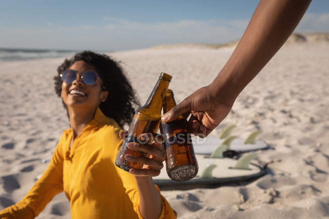 Side view of young African American couple toasting beer bottle at beach on sunny day — стоковое фото