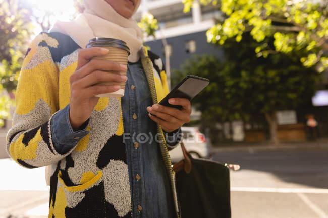 Vista a basso angolo della donna che utilizza il telefono cellulare mentre tiene un caffè in strada in una giornata di sole — Foto stock