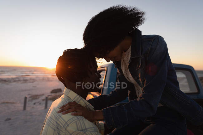 Side view of couple romancing on the beach near car at sunset — Stock Photo