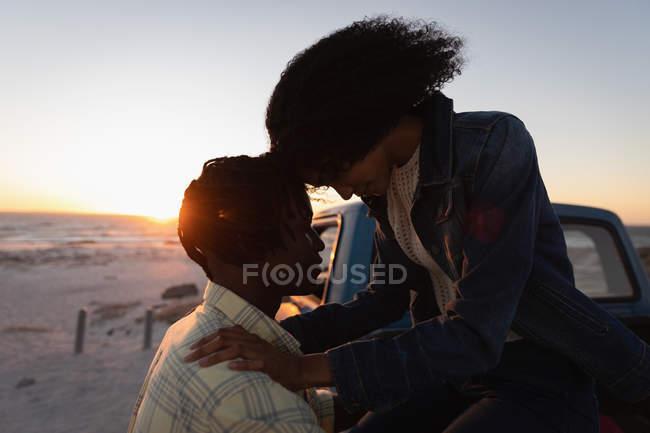 Vista laterale di coppia romancing sulla spiaggia vicino auto al tramonto — Foto stock