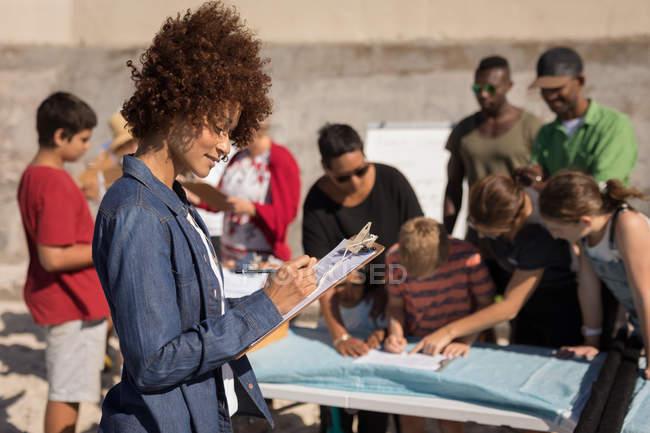 Seitenansicht der jungen gemischten Rasse Frau schreiben auf Zwischenablage am Strand an einem sonnigen Tag. Gruppe von Multi-Ethnischen arbeitet an den Hintergründen — Stockfoto