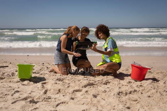 Frontansicht einer Gruppe von multiethnischen Freiwilligen, die auf den Knien sitzen, um den Strand an einem sonnigen Tag zu reinigen — Stockfoto