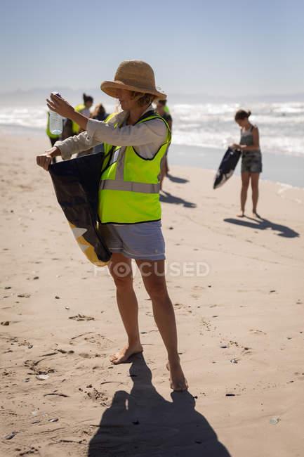 Vorderseite der jungen kaukasischen weiblichen Freiwilligen Reinigung Strand an einem sonnigen Tag — Stockfoto