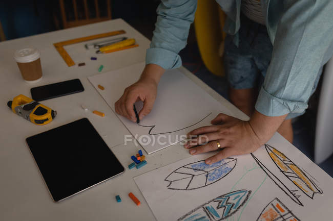 Mid section of man drawing surfboard sketch in a workshop. Tablet, coffee, ruler, pencils, crayons, paper, and mobile phone are displayed on the table. — Stock Photo