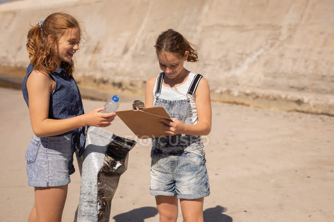 Front view of young Caucasian volunteers holding plastic bottle, clipboard and plastic bag on beach on a sunny day — Stock Photo