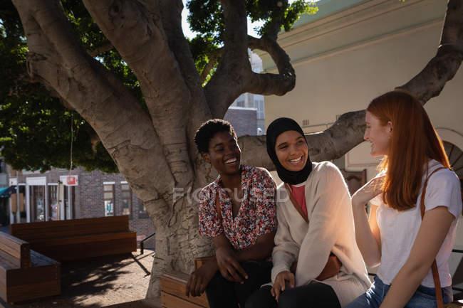 Vista lateral de felices amigas de raza mixta interactuando entre sí mientras están sentadas bajo el árbol - foto de stock