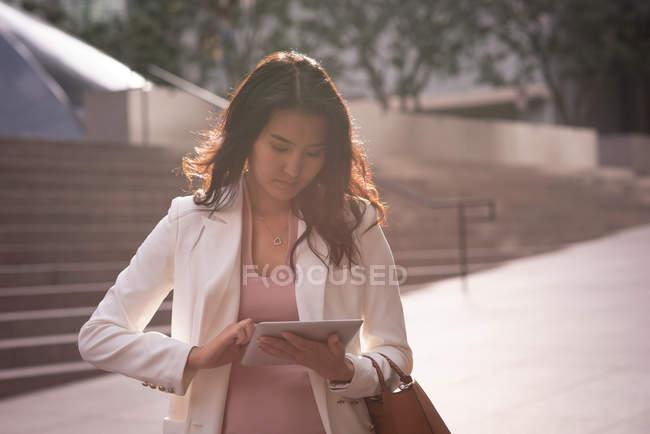 Vista frontale della donna asiatica utilizzando tablet digitale mentre in piedi sul marciapiede in una giornata di sole — Foto stock
