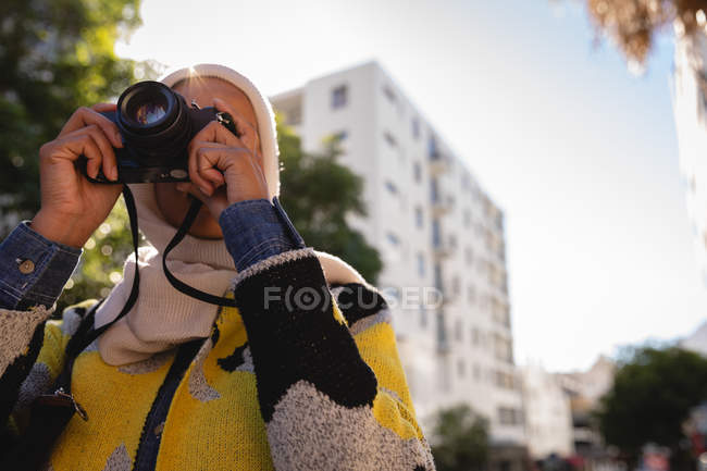 Low angle view of a mixed-race woman taking a picture with her digital camera at street on a sunny day — Stock Photo