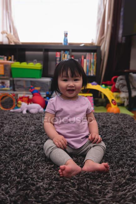 Портрет малого мила Азіатська дитина дивиться на камеру і сидячи на килимі в домашніх умовах — стокове фото