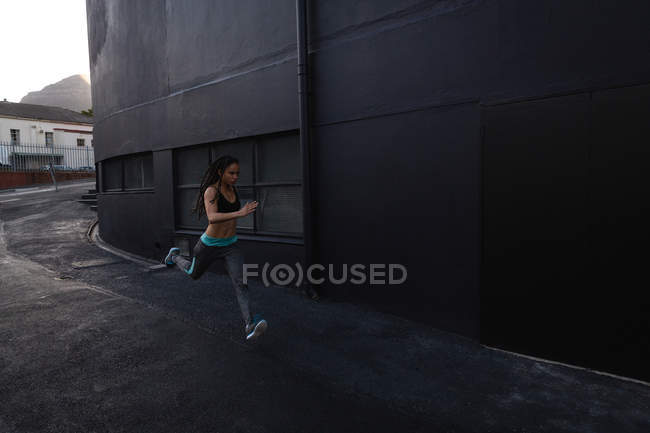 Вид сбоку молодой женщины смешанной расы, бегущей по улице в городе — стоковое фото