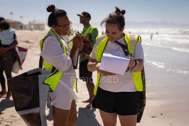 Frontansicht von glücklichen multiethnischen Weiblichen, die über Zwischenablage diskutieren, während die anderen Freiwilligen am Strand putzen — Stockfoto