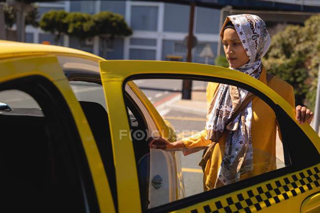 Vista frontal de la pensativa mujer de raza mixta subiéndose al taxi en la calle - foto de stock