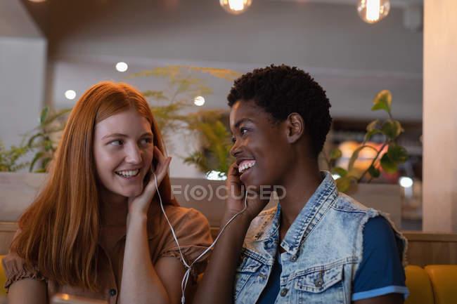 Vista frontal de amigas femeninas de raza mixta escuchando música con teléfono en el restaurante - foto de stock