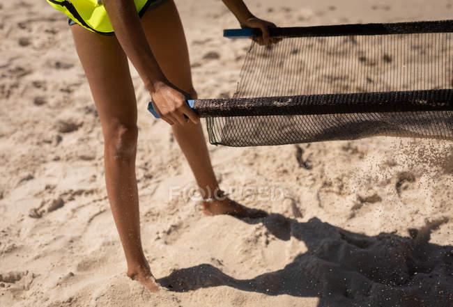 Geringer Teil der weiblichen Freiwilligen hält ein spezielles Sieb am Strand an einem sonnigen Tag — Stockfoto