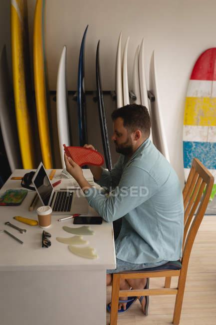 Вид сбоку кавказца, осматривающего плавник в мастерской — стоковое фото