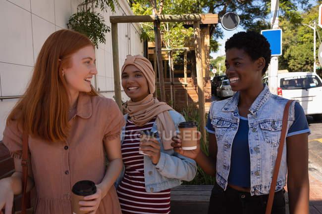 Первый взгляд на счастливую молодую смешанную расу подруги взаимодействуют друг с другом за чашечкой кофе на улице — стоковое фото