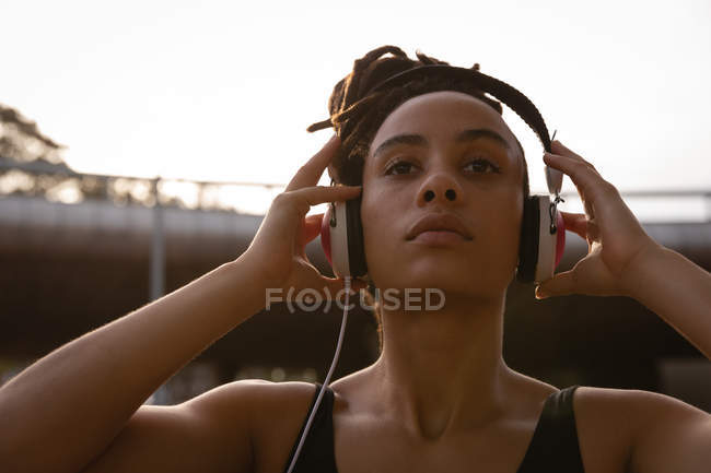 Close up of young Mixed race woman listening music on headphones in the city — Stock Photo