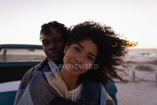 Frontansicht eines romantischen afrikanisch-amerikanischen Paares, das sich bei Sonnenuntergang am Strand am Auto lehnt — Stockfoto