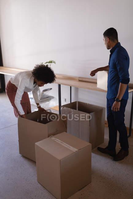 Vue de côté des jeunes gens d'affaires de course mixte déballant des boîtes dans un nouveau bureau — Photo de stock
