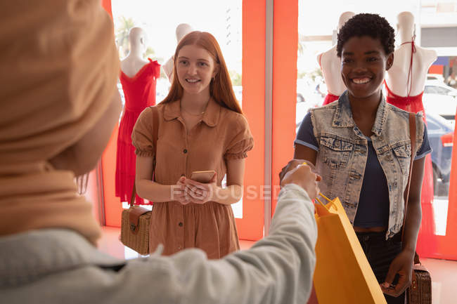 Visão traseira do saco de manipulação do proprietário da loja feminina para jovem bela raça mista cliente feminino na boutique — Fotografia de Stock