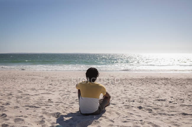 Rear view of young African American man relaxing at beach on a sunny day — Stock Photo