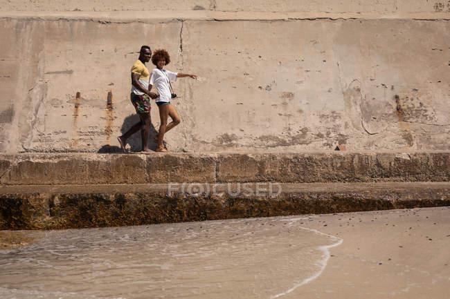 Вид сбоку симпатичной многоэтнической пары, гуляющей вместе по набережной на пляже в солнечный день — стоковое фото
