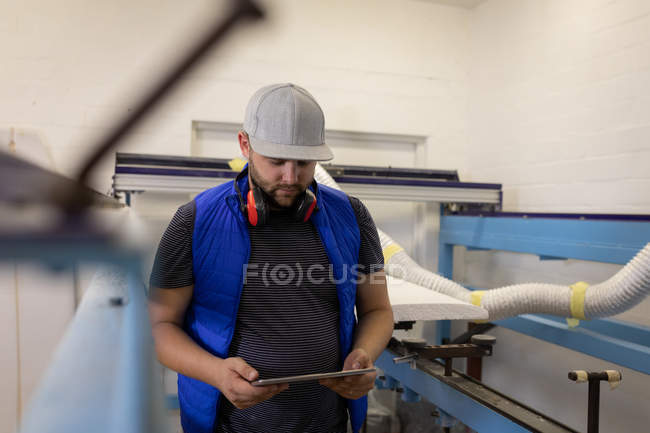 Front view of Caucasian man with cap and earmuffs standing and using digital tablet in workshop — Stock Photo